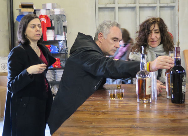 Sofia Perez, Ferran Adrià, and Isabel examine a bottle of J. Rieger whiskey.